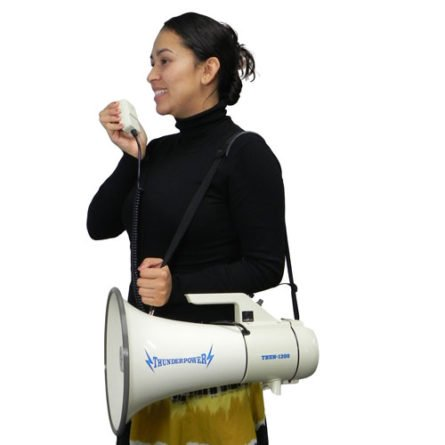 Woman carrying ThunderPower 1200 with shoulder strap and using the palm mic